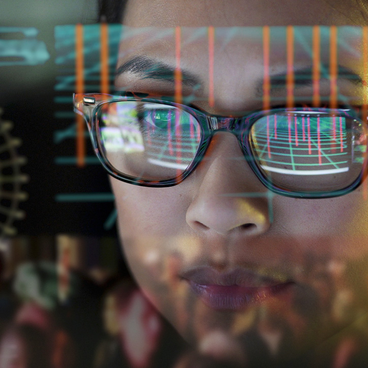 Woman with glasses looking through reflections of computer data