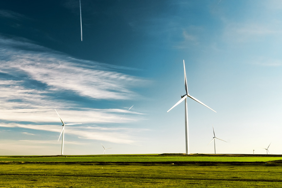 Green field with wind turbines against a blue sky